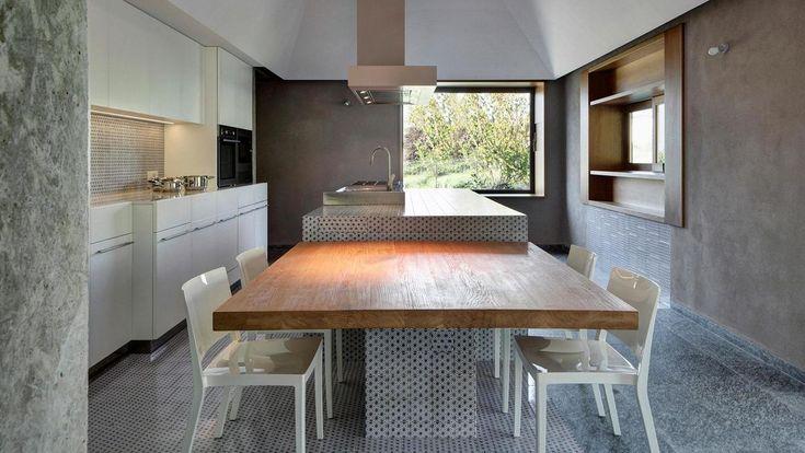Брутально большой кухонный остров с обеденным столом на кухне интерьером намекающей на кухню общепита с окошком для выдачи блюд. .