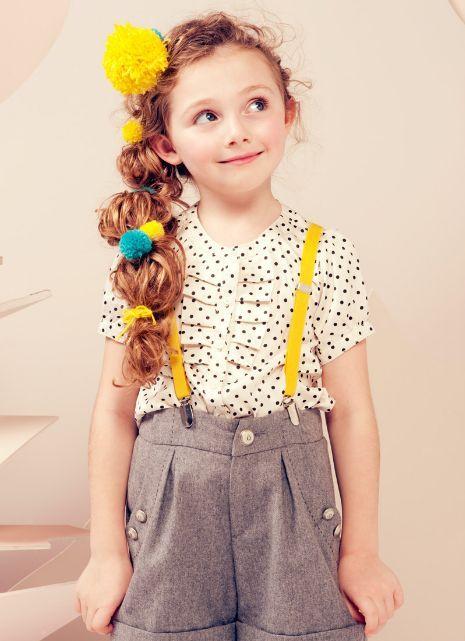 黄色とグリーンのポンポンを髪の毛に編み込んでいます。黄色のサスペンダーの色と合わせているところが素敵!
