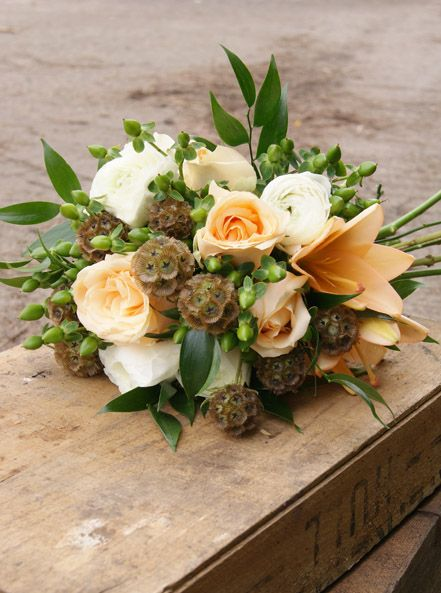 Lush, textural peach and green hand-tied bridal bouquet with roses, lilies, green hypericum berries, scabious stellata seedheads and white ranunculus. Florissimo, Shropshire