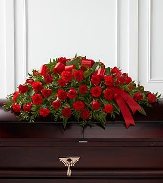 """Rich red roses and carnations are gorgeously arranged amongst lush greens and accented with a red satin ribbon to create the ideal adornment for their casket at their final farewell service.  Approximately 40""""L x 26""""W"""