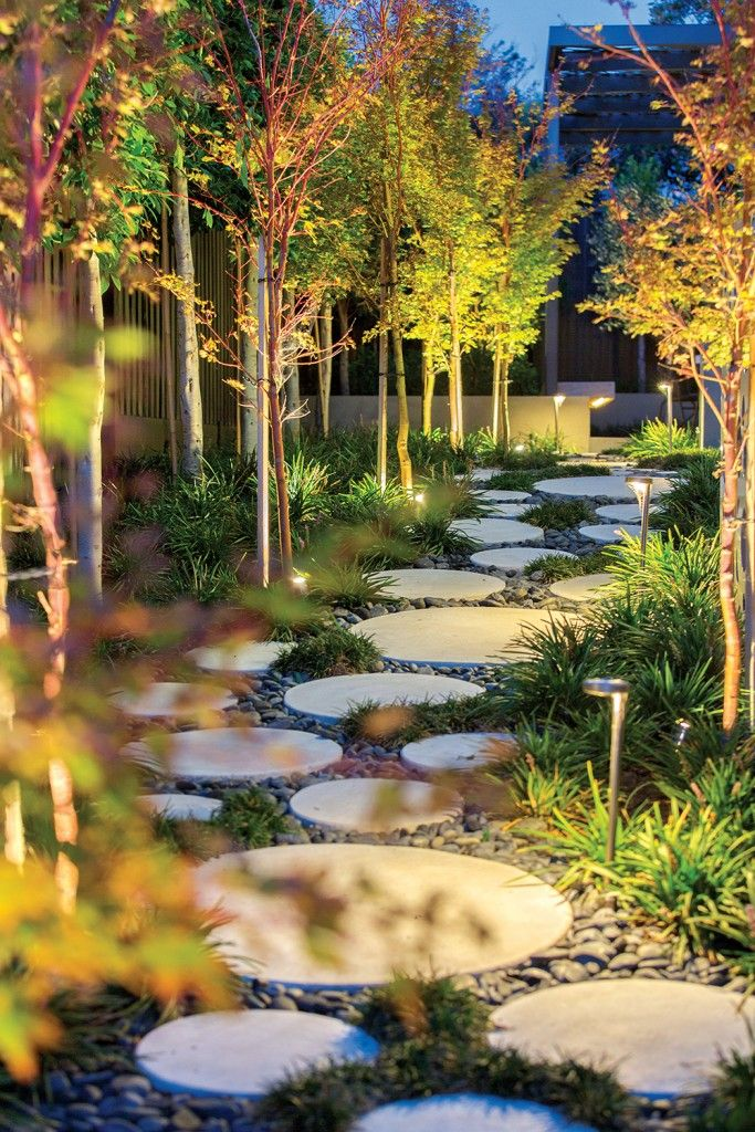 The path between sections of the yard is filled with subtle lighting tricks, glowing the surrounding maples from beneath. The large concrete discs are set into a bed of smooth stones, perfectly illustrating the thematic combination of sharp architecture and natural elements.