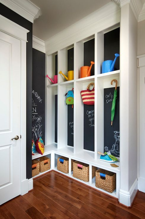 Family friendly mud room features floor to ceiling built-ins over chalkboard painted walls with cubbies and coat hooks over lower storage bench lined with seagrass bins.