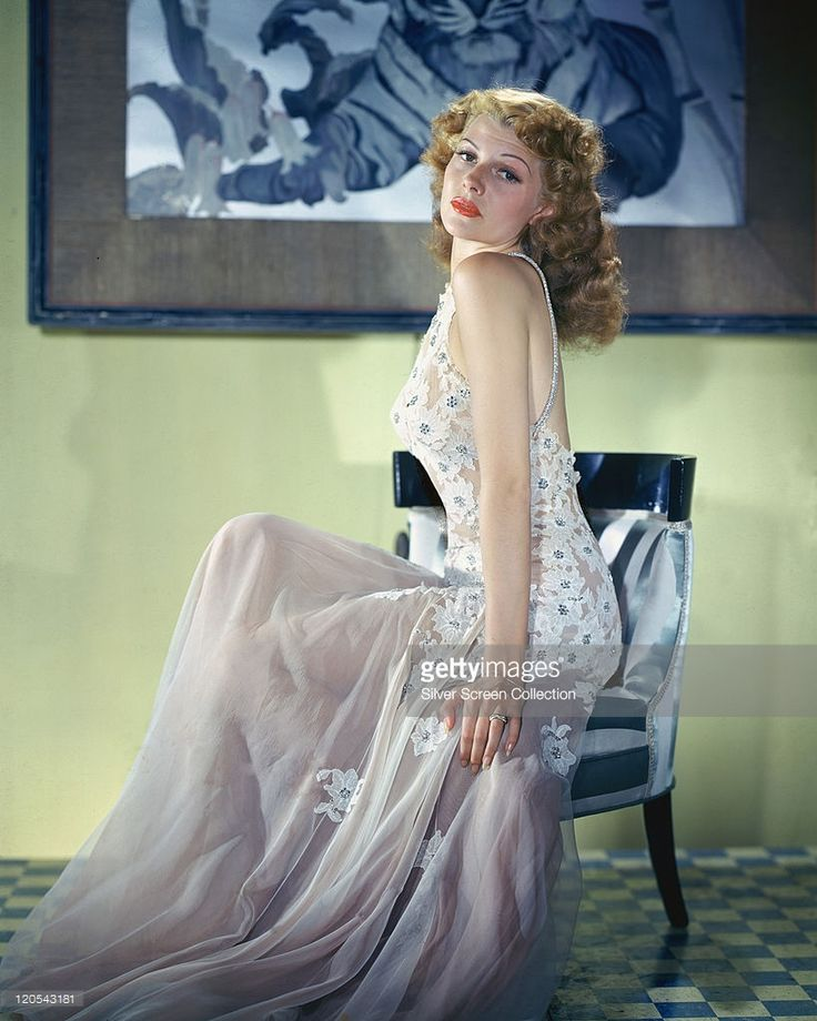 Rita Hayworth (1918-1987), US actress and dancer, wearing a long dress, with a white lace bodice, with floral motifs, and a white chiffon skirt, sitting in a chair in a studio portrait, circa 1950.