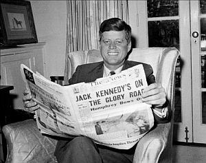 May 1960: John F. Kennedy at home in Washington, D.C. reading newspaper about his victory in the West Virginia primary and rival Hubert Hump...