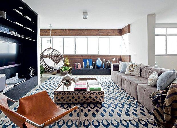 Apenas apaixonada por esse tapete, essa mesa de centro, essa cadeira redonda pendente do teto e o revestimento da parede. Só.