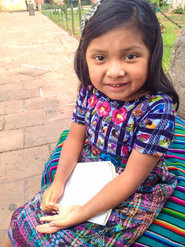 In Antigua Guatemala, Lili sits in the park and scribbles on her notepad, as her Mom sells handknit fabrics to tourist passing by! <3