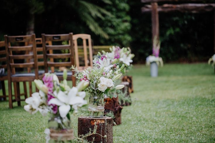 Line the aisle with log stumps and flowers for rustic charm vibes. The perfect New Zealand wedding!