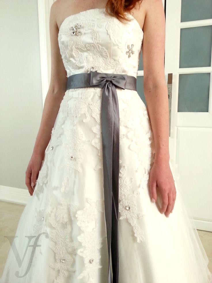 Vestido de noiva Love Tie modelo tomara que caia em cetim com tule contendo aplicação de rosas de renda em alto relevo. Com laço de Cetim na cor grafite claro na cintura.