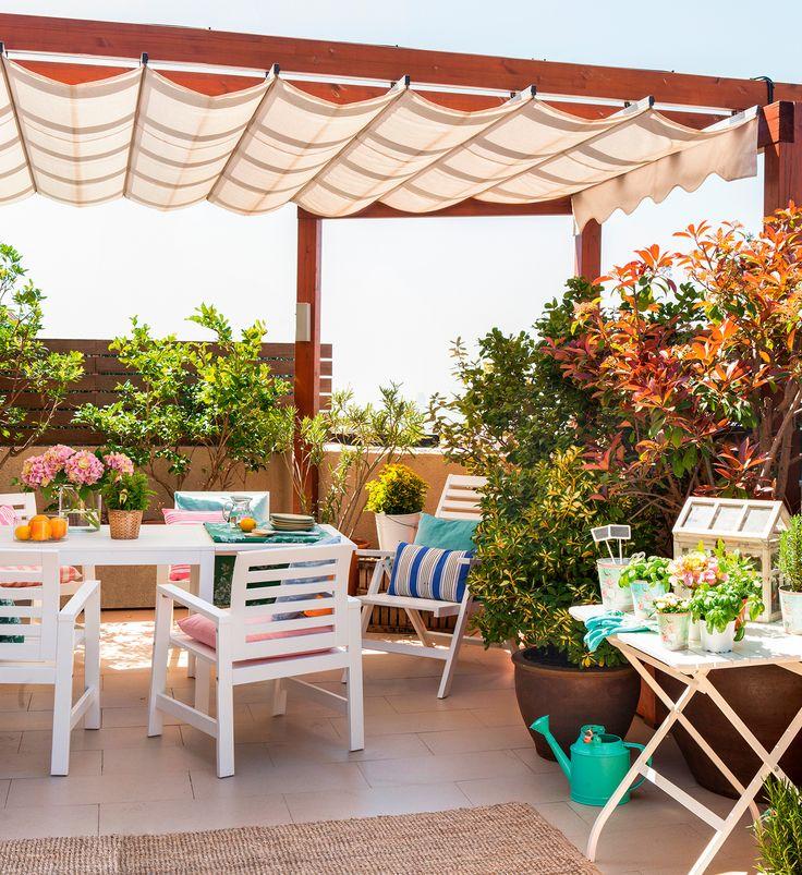 Terraza con pérgola, comedor exterior en blanco, alfombra de sisal, mesa plegable, cojines a rayas, plantas y flores
