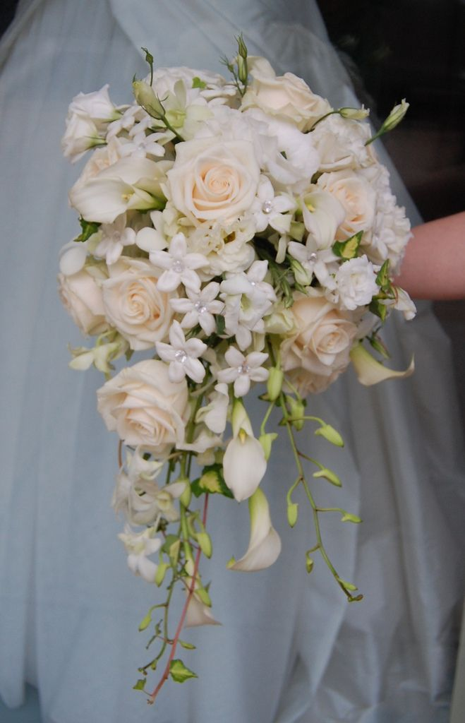 White flowers such as roses, mini callas, stehanotis and orchid create this simple but elegant bridal bouquet www.sendingsmiles.com