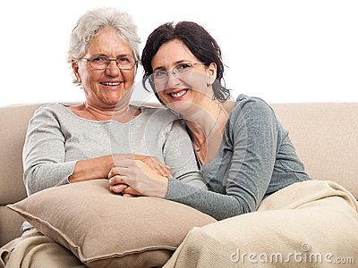 Family portrait, senior mother and adult daughter sitting, smiling, indoor with pillow and blanket. Isolated on white.