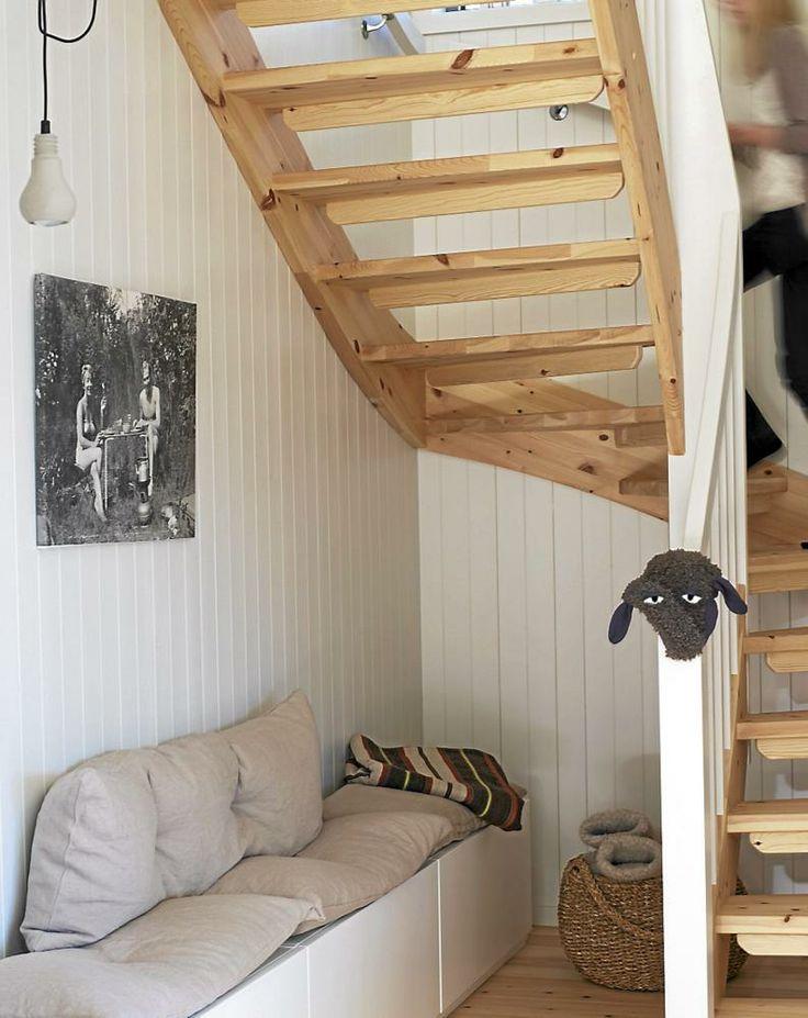 ENTRÉ: I gangen har beboerne laget en sittebenk av kjøkken overskap fra Ikea. Betonglampen Edison er fra kvist-visdal.no. Trappen er fra Vegårdshei Trappesnekkeri. Sauehodet er egentlig ment for sykkelseter. Kurven under trappen har tøfler i forskjellige størrelser til gjestene.