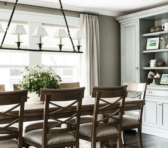 Rustic elegance dining room - nailhead trim on seat cushions contrast the farmhouse style