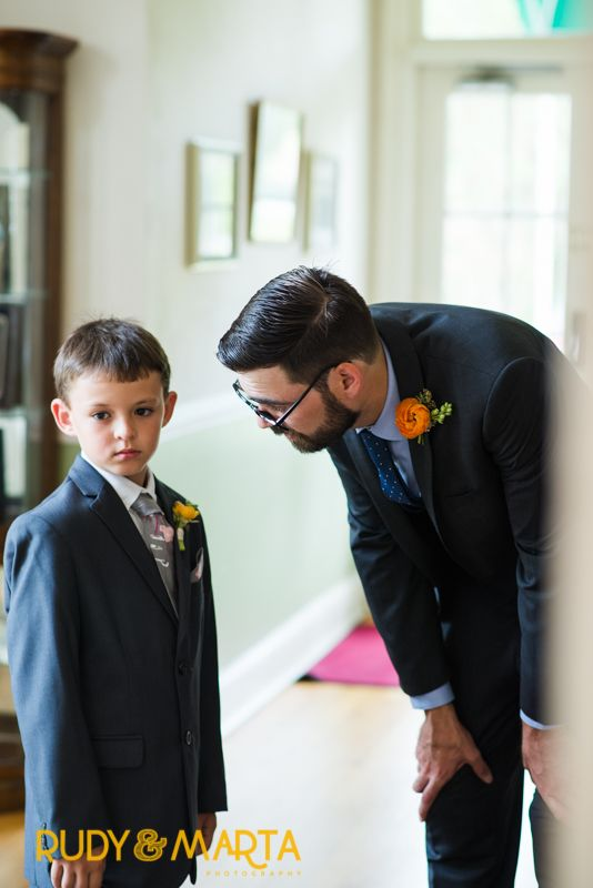 the groom and ring bearer each wear boutonnieres of orange ranunculus.