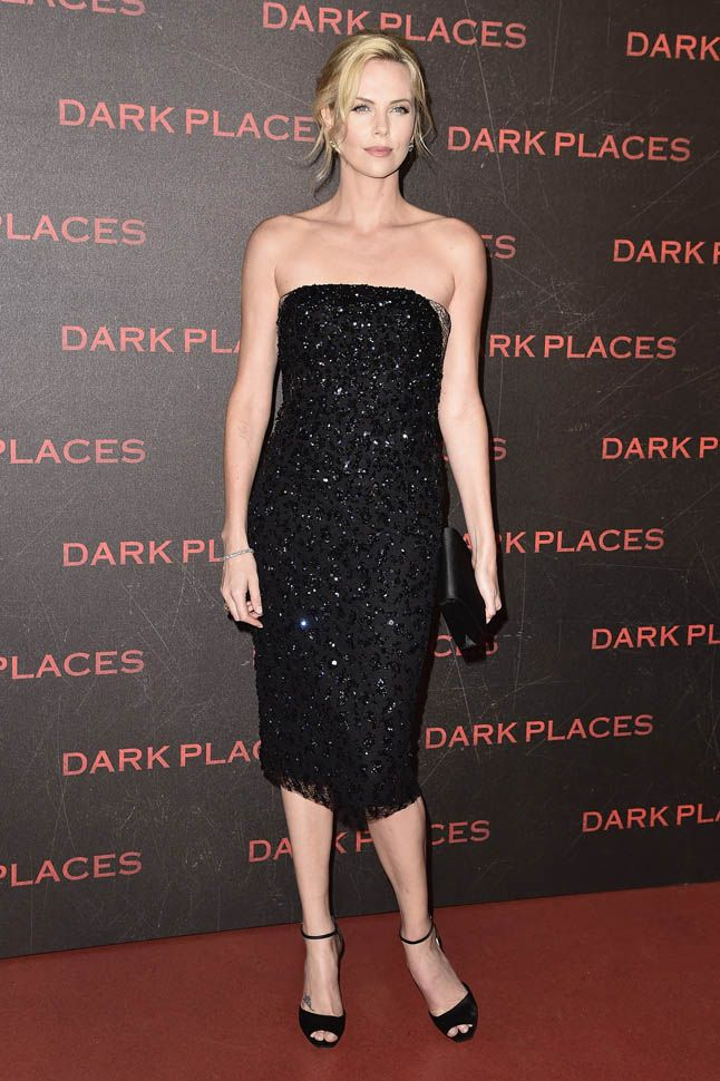 "To αλάνθαστο μαύρο βραδινό στράπλες: η Σαρλίζ Θερόν με ολοκέντητη δαντελένια δημιουργία Dior και λιτά πέδιλα στην πρεμιέρα του φιλμ μυστηρίου ""Dark Places"" στο Παρίσι. Η 39χρονη νοτιοαφρικανή καλλονή κάτοχος Οσκαρ, ζει στο Λος Αντζελες και παραμένει μούσα του οίκου Dior.Είναι εναντίον της βίας και υπεραμύνεται των δικαιωμάτων γυναικών και ζώων, ενώ ο δεσμός της με τον Σον Πεν πάει για επισημοποίηση."