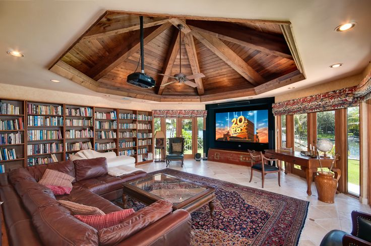 Interesting approach to a combined library and media room. Drapes allow full control of room light. Coffered ceiling mirrors shape of room outline. Huge bookcase.