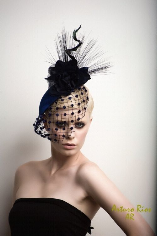 Cocktail Hat- Fascinator- Headpiece - vintage materials w/ a modern look.  round base covered w/ Navy blue taffeta, adorned w/ 2 silk flowers on top, also somoe horsehair & a twisted feather in the center; vintage veil w/ navy velver dots from the 40's as a final accent  $ 179--, Arturo Rios via Etsy.