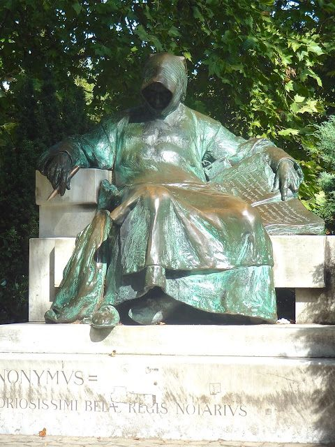The bronze sculpture of 'Anonymous' in monk's habit with the cowl obscuring his face, located in the courtyard of Budapest's Vajdahunyad Castle