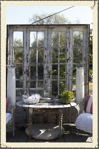 Re-purposed old French doors used for pseudo-wall/screen in the patio setting - could also start trailing vines to drape over