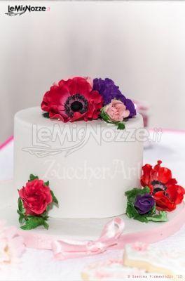 http://www.lemienozze.it/operatori-matrimonio/catering_e_torte_nuziali/torte-di-matrimonio-varese/media/foto/6 Torta nuziale decorata con fiori freschi viola, rosa e rossi.