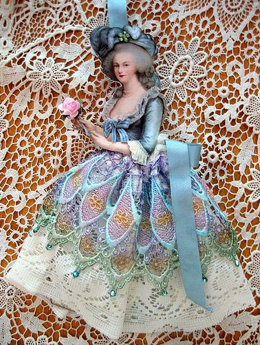 Marie Antoinette paper doll with bits of lace and ribbon for her dress