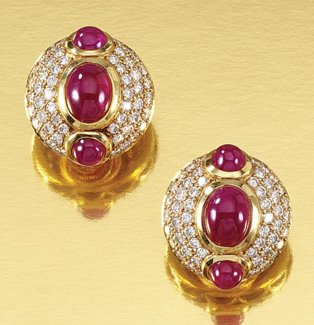 PAIR OF RUBY AND DIAMOND EAR CLIPS, BULGARI Each of bombé design, collet-set to the centre with a line of three cabochon rubies, bordered by three concentric rows of brilliant-cut diamonds, signed Bulgari and numbered, maker's marks, French assay marks.