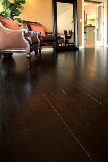 This was a red oak wood floor that we stained with Dura Seal ebony stain. Afterwards the floor was coated with Chromakey Lamp Black/Burnt Umber to achieve an even darker color that still reflected light. This picture shows a close up of how the color conceals the walnut pegs from the floor.