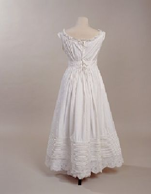 """Petticoat back 1828-1835 (1947.1934) The waistband, in this case, is just higher than the natural level. Higher waists like this were a fashionable feature at the beginning of the nineteenth century, intended to suggest an """"Empire"""" silhouette, but by 1830 they had descended to a natural line again. This piped or rouleaux hem also gives more fullness to the skirt than was fashionable during the first decade of the nineteenth century."""
