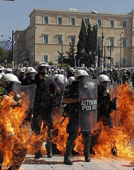 A fire bomb explodes among riot police during clashes in Athens