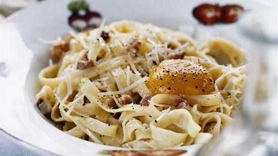 Koka pastan enligt anvisning på paketet. Stek pancetta och vitlök i lite av olivoljan. Blanda grädden med 2 äggulor. Blanda den stekta pancettan med nykokt tagliatelle och gräddblandningen. Smaka av med salt, svartpeppar och lite parmesanost.  Lägg 1 äggula på varje portion och strö på lite extra parmesan. Ringla över lite olivolja.