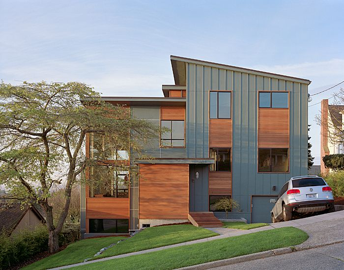 The exterior of this modern remodel of a post-war split level is clad in…