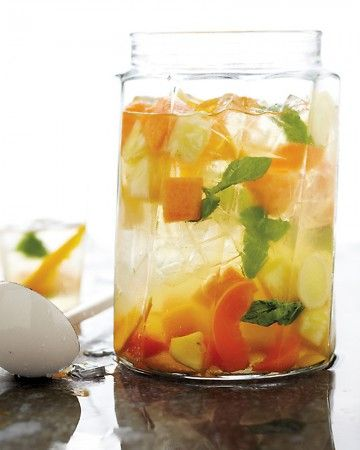 Summer Fruit Sangria - 6 cups assorted fruits (such as mango, pineapple, cantaloupe, and apricot), sliced or cut into chunks   1/4 cup thinly sliced peeled fresh ginger   1 to 1 1/2 cups fresh basil or mint leaves   1/2 cup orange liqueur, such as Cointreau   1 bottle crisp white wine, such as Sauvignon Blanc or Pinot Grigio   3 tablespoons fresh lemon juice (from 1 lemon)   Ice