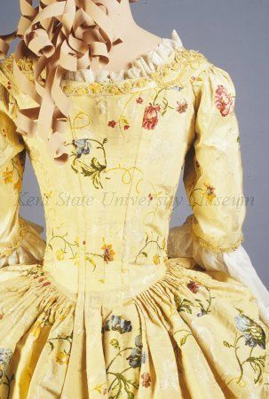 Back view, robe à l'anglaise, England, c. 1770. Yellow silk, supplementary wefts of blue, red, burgundy, yellow flowers, lined with linen. Probably altered from a mid 18th century robe à la française and restyled as a robe à l'anglaise with pleats at center back stitched down at the waist. Worn as formal day or evening wear.