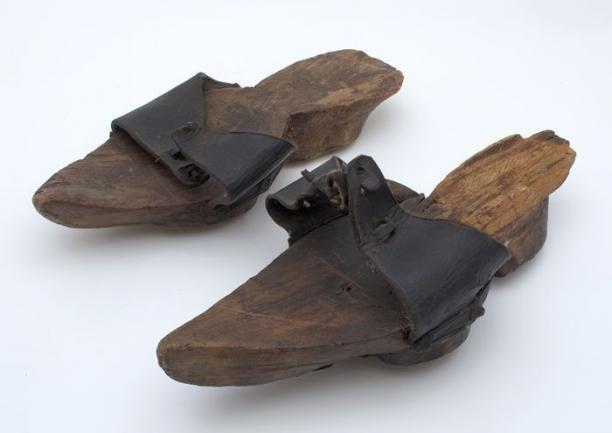 Twee leren trippen met houten zolen en leren band over de tenen Twee houten…