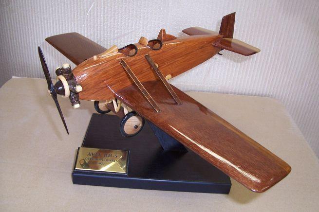 Model vojenského letadla ze dřeva ve vzletové poloze včetně stojánku s věnováním.  AVIA-BH-5
