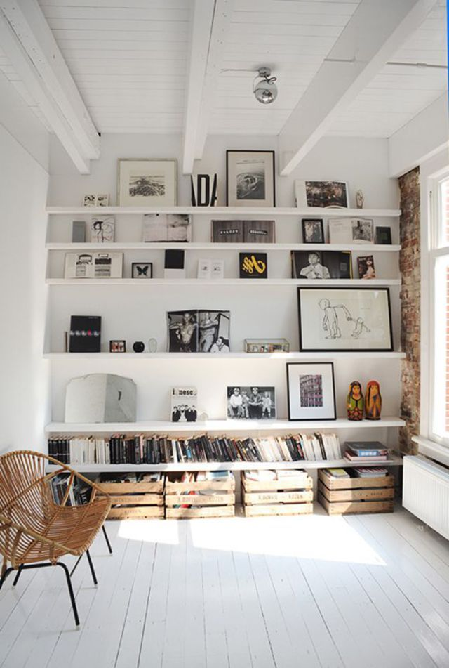 Dans cette pièce, quelques cagettes en bois font office de bibliothèque récup' et, au mur, des étagères accueillent livres et cadres