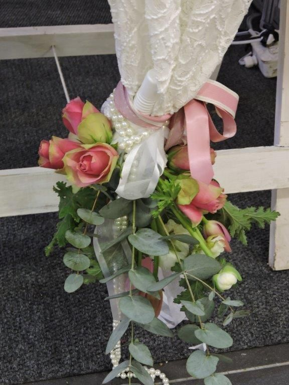 A lace runner edged with flowers and pearls