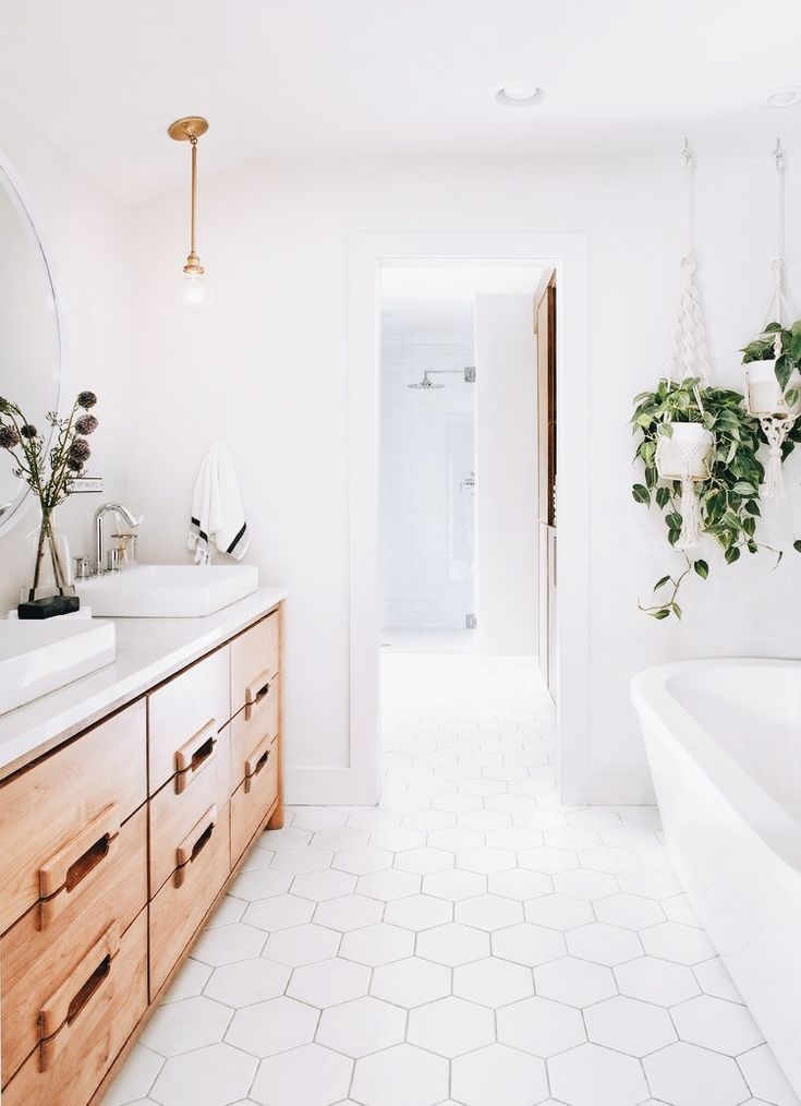 Flawless white bathroom. Beautiful white tile and tub. Accents of wood and plants