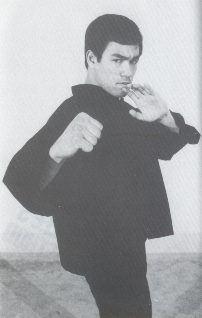 """Bruce Lee """"'The Way of the Intercepting Fist.' Is Jeet Kune Do."""" His pose and positional stance is leading with the right fist forward and left open palm guard to the rear symbolizing 'The Way of the Intercepting Fist.' Jeet means 'to stop, to stem, to intercept,' while Kune means 'fist' or 'style,' and Do means 'the way' or 'the ultimate reality.' In other words - 'The Way of the Intercepting Fist.' A Traditional Boxer's southpaw stance."""