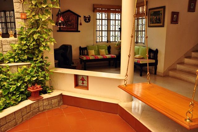 Open Courtyard (mittham) within house. Creeper plant. Red oxide flooring. Jhoola.