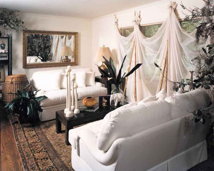 Awesome idea for window curtains!  Look closely.  They aren't hung on the wall, but held up by bamboo sticks!      This Bohemian styled space utilizes family antiques with eclectic accessories, and is accented with the mosquito netting styled window treatments held by bamboo poles.