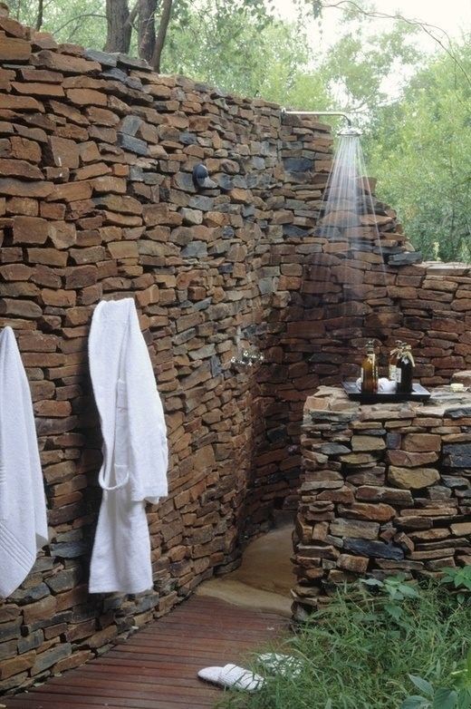 Outdoor shower.  Rock wall with concrete basin?
