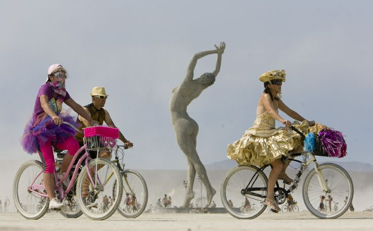 Burning Man participants pedal across the playa on Aug. 31, 2013. (Rick Egan  | The Salt Lake Tribune)