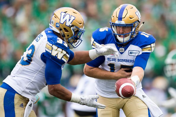 Matt Nichols hands the ball off to Andrew Harris of the Winnipeg Blue Bombers in the game between the Winnipeg Blue Bombers and Saskatchewan...