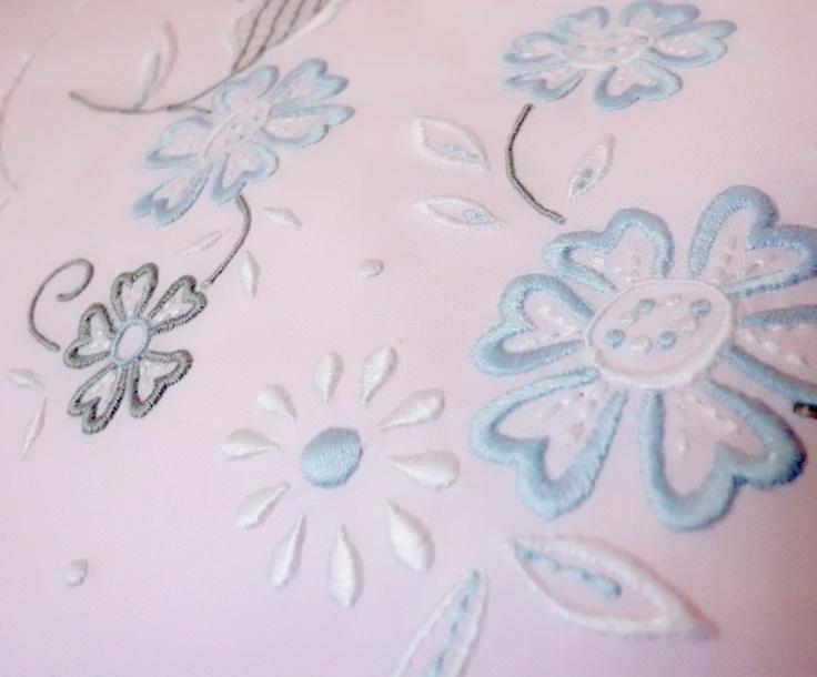 Juego de cama bordado en hilo de varios colores sobre tela rosa
