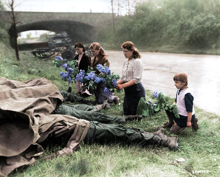 Russian women and children recently liberated from a Nazi concentration camp lay flowers at the bodies of four dead American soldiers. Eyewitnesses reported the Americans were murdered by German officers after they had surrendered in Hilden, Germany (1945)