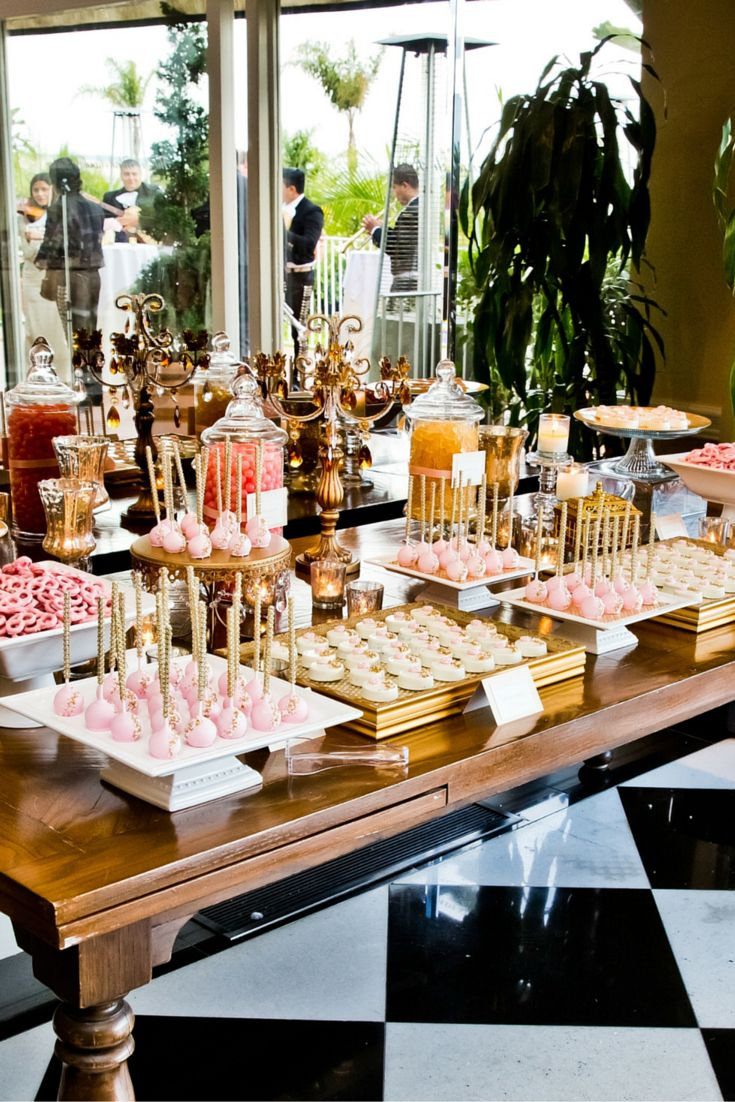 A fun and delicious gold and bubble gum pink dessert bar for a glamorous wedding at La Valencia Hotel in La Jolla - Guests loved the cake pops with crystal sticks and chocolate-covered Oreos embellished with edible glitter and gum paste roses - Visit our blog for more yummy pictures! Photo by True Photography - Styling by San Diego wedding designer and planner Sabrina Cadini with La Dolce Idea