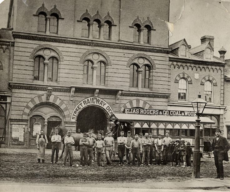 This group photo of the Street Railway Department was taken outside Yorkville Town Hall on the west side of Yonge at Collier Ave.  In the background you can see a horse-drawn streetcar (with roof advertising) and a gas streetlamp. There are five barefoot boys, a farrier and at least one Asian man in the photo from 1870s Toronto.