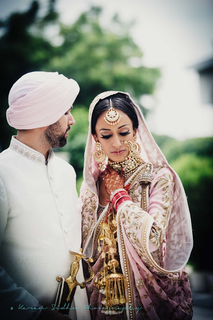 Sikh Wedding Bride - Beautiful Candid Shot of the Couple | WedMeGood | Sikh Bride in a Pastel Pink Lehenga with Copper Embroidery Wearing a Choker and Gold Kaleere, Groom in an Off-White Sherwani and Light Pink Turban #wedmegood #indianwedding #indianbride #lehenga #candid