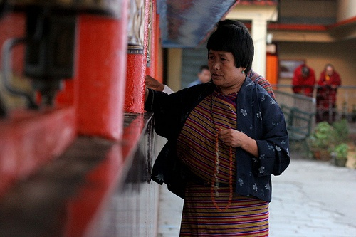 Prayer on Wheels. A buddhist woman turns the prayer wheels at Do-Drul Chorten